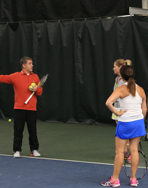 Lake Bluff tennis pro teaching an adult class on the court.